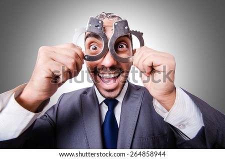 Funny businessman with handcuffs on white - stock photo