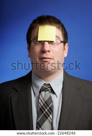 Funny businessman with yellow sticky note on forehead - stock photo