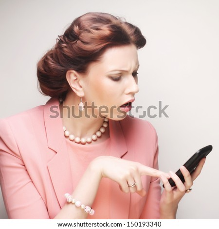 funny businesswoman with mobile phone over gray background - stock photo