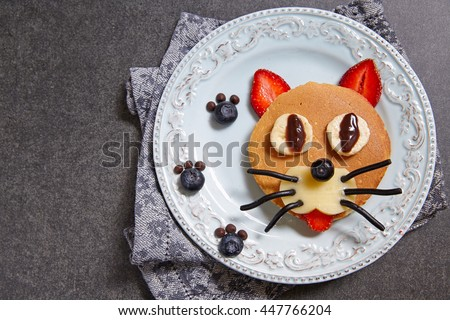 Funny cat pancake with berries for kids breakfast - stock photo