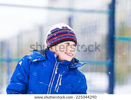 Funny cheerful boy in jacket and hat playing outdoors in winter laughing - stock photo