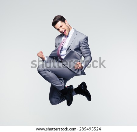 Funny cheerful businessman jumping in air over gray background - stock photo