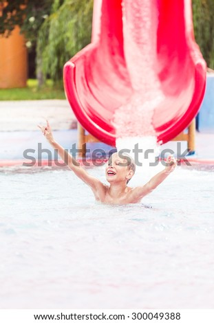 Funny cheerful child enjoying summer vacation in water park taking a ride in excitement.  - stock photo