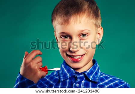 Funny cheerful child holding a screwdriver smiling. Help and support concept.  - stock photo