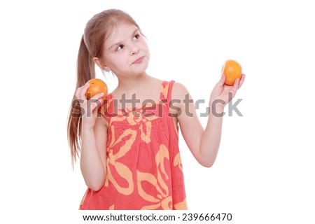Funny cheerful positive little girl holding mandarins - stock photo