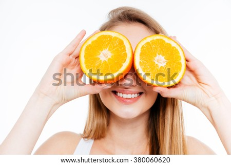 Funny cheerful young woman holding two halves of orange agains her eyes over white background