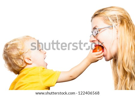 Funny child boy feeding young woman with tomato, isolated on white background with copy space. - stock photo