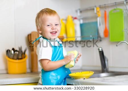 Funny child boy washing dishes in kitchen - stock photo