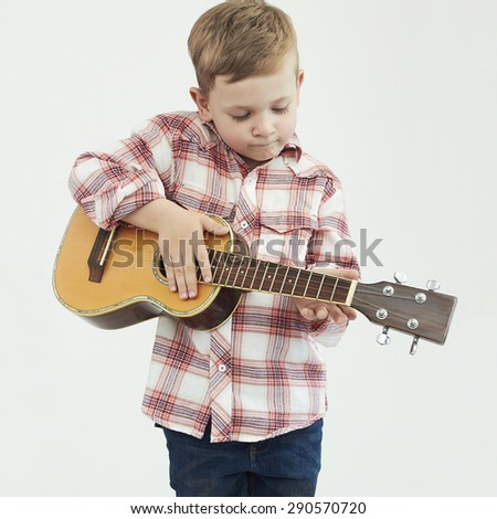 funny child boy with guitar.fashionable country boy playing music - stock photo