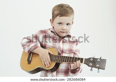 funny child boy with guitar.ukulele guitar. fashionable country boy playing music - stock photo