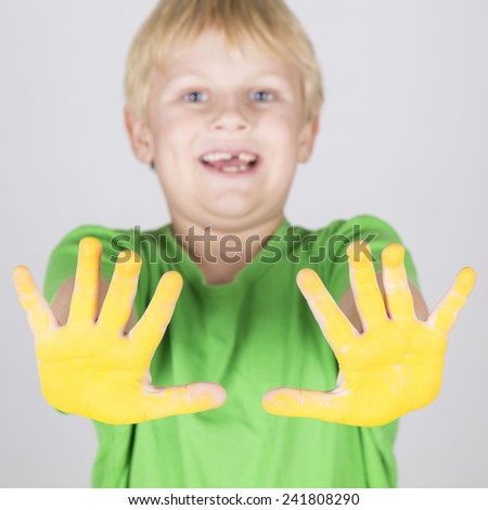 Funny child boy with hands painted with color yellow - stock photo