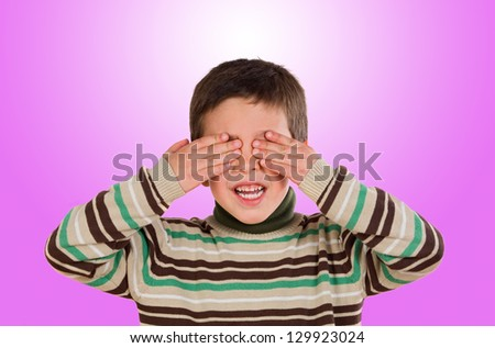Funny child covering his eyes on a pink background - stock photo