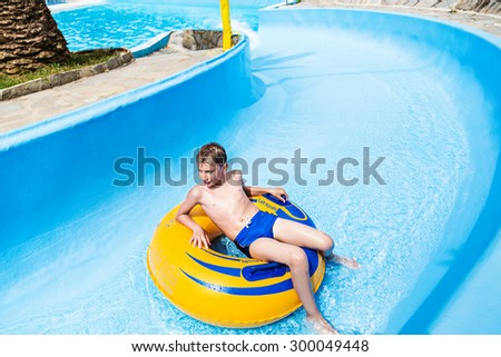 Funny child enjoying summer vacation in water park taking a ride on yellow float
