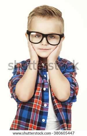 Funny child.fashionable little boy in glasses, jeans, white t-shirt and plaid shirt.stylish kid in sport shoes. fashion children closes his ears  hands