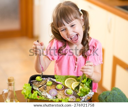 Funny child girl and grilled fish at kitchen. Healthy eating seafood. - stock photo