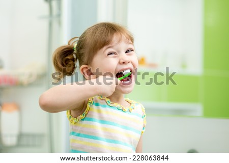Funny child girl brushing teeth in bathroom - stock photo