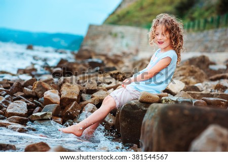 funny child girl playing with water splash on the beach. Traveling on summer vacation. Happy childhood concept.