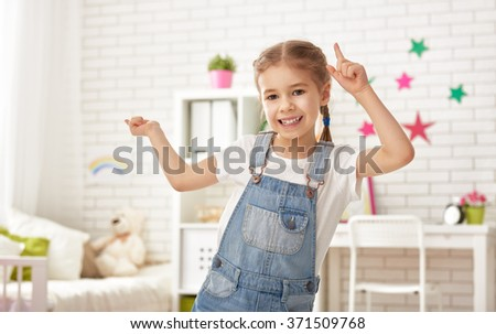 funny child girl plays at home. girl having fun and dancing. recreation and entertainment at home. - stock photo