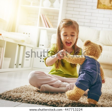 funny child girl plays at home. girl having fun with teddy bear. recreation and entertainment at home. - stock photo