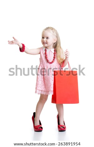 Funny child girl trying her mom's red accessories and shoes on - stock photo
