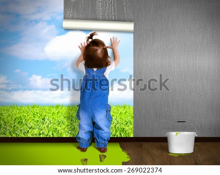 Funny child hanging wallpaper, doing repairs. Eco house concept. - stock photo