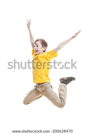 Funny child in bright yellow t-shirt jumping and laughing on white background