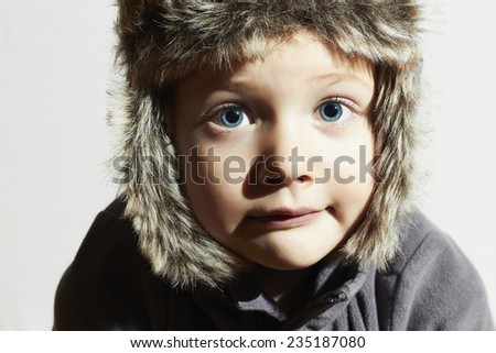 Funny child in fur Hat.casual winter style.close-up portrait of little boy.children emotion.hat ear flaps.Big blue eyes - stock photo
