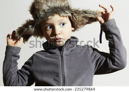 funny child in fur Hat.Kids fashion casual winter style.little boy.children emotion.hat ear flaps - stock photo