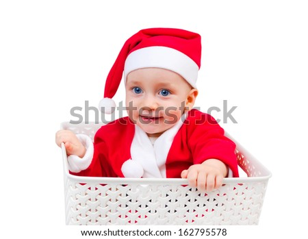 Funny child in Santa Clause cap sitting in a box isolated on white background - stock photo