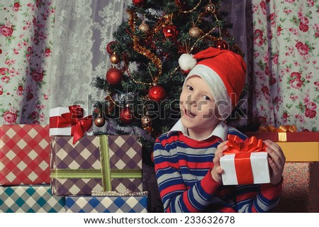 funny child in Santa red hat holding Christmas gift box with red bow in hands. Christmas concept. - stock photo