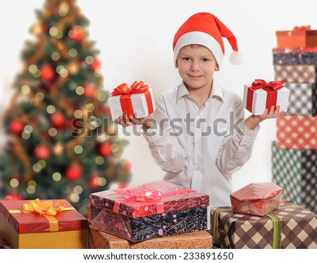 funny child in Santa red hat holding Christmas gift boxes with red bows in hands. - stock photo