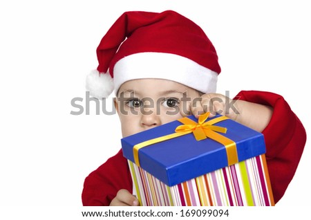 funny child in Santa red hat holding Christmas gift in hand. Christmas concept.  - stock photo