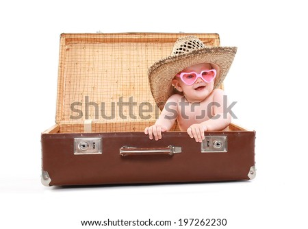 Funny child in sunglasses and summer straw hat looks out of a suitcase, tours, travel, vacation - concept - stock photo