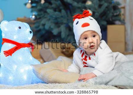 Funny child lying on bed next to teddy bear. Christmas. New Year concept