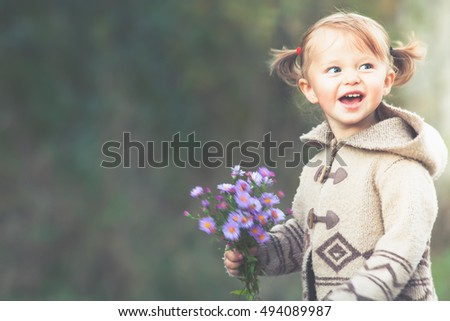 Funny child outdoor at flowers field holding flowers. Autumn season. Happy Family Values. Baby girl. Children care. International Children's Day at 20 November or June 1 Universal Children's Day