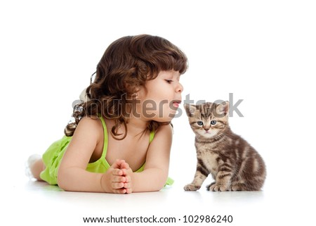 funny child playing and kissing Scottish kitten - stock photo