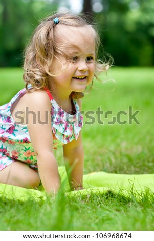 Funny child playing in grass - stock photo