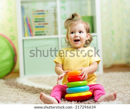 funny child playing with toy indoor - stock photo