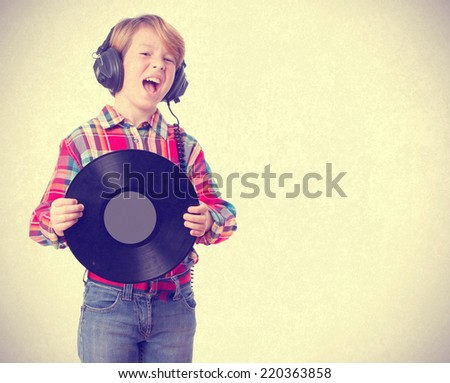 Funny child singing with an headphones and a vinyl - stock photo