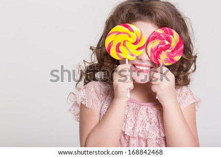 Funny child with candy lollipop, happy little girl eating big sugar lollipop, kid eat sweets. surprised child with candy. isolated on white background, studio.  - stock photo