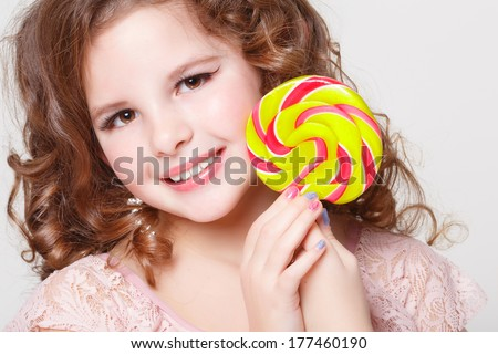 Funny child with candy lollipop - unhealthy eating, happy little girl eating big sugar lollipop, kid eat sweets. surprised child with candy. isolated on white background, studio. series - stock photo