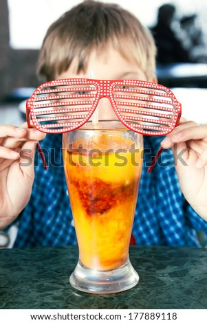 Funny child with party sunglasses drinking a fruit cocktail from a big glass. Creative drink concept.  - stock photo