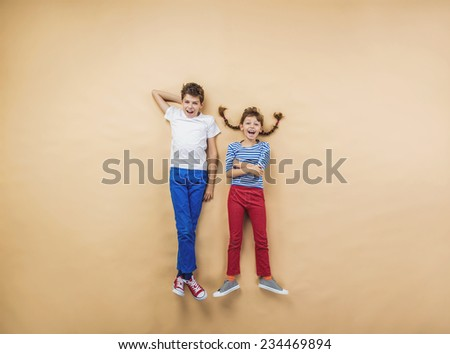Funny children are playing together. Lying on the floor. - stock photo