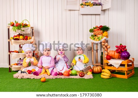 Funny children cooking in kitchen. small cute children in costume of Cook. small children in a suit of the cook in the kitchen preparing soup. - stock photo