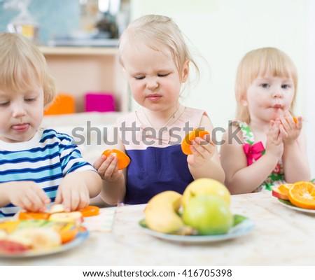 Funny children eating fruits in kindergarten - stock photo
