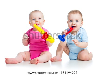 Funny children girl and boy playing with musical toy. Isolated on white background