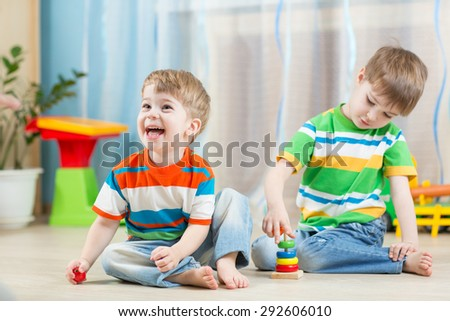 funny children play with toys indoor - stock photo