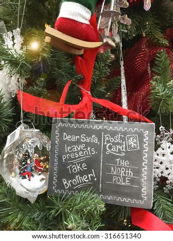 Funny Christmas sign on tree with words  Dear Santa leave presents take brother  - stock photo