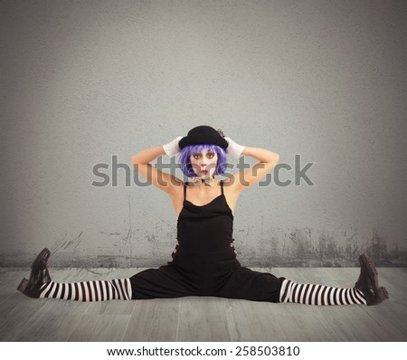 Funny clown dancer makes a big split - stock photo