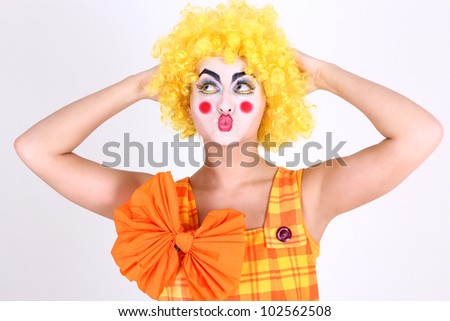 Funny clown in costume with bow and make-up
